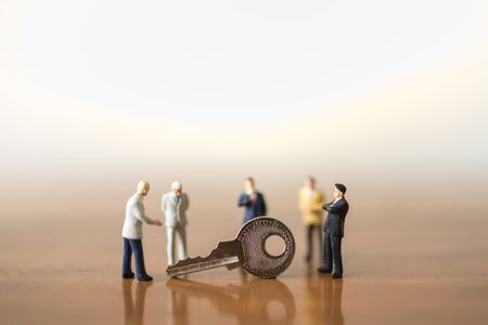 Business, Planning and Security Concept. Group of businessman miniature figures people standing and meeting with silver key on wooden table with copy space. Zdjęcie Seryjne