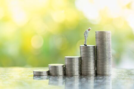 Business, Money Investment and Planning Concept.  Close up of businessman miniature people figure standing on stack of silver coins with green anture background with copy sapce. Zdjęcie Seryjne