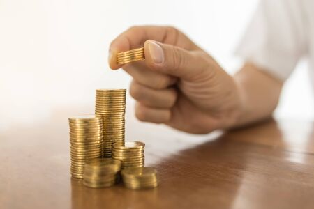 Business, Money, Finance, Secure and Saving Concept. Close up of man hand holding and put five coins to top of stack of gold coins on wooden table.