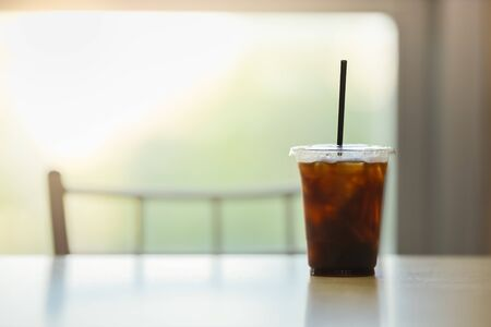 Close up of take away plastic cup of iced black coffee (Americano) in restaurant on table with copy sapce. Zdjęcie Seryjne