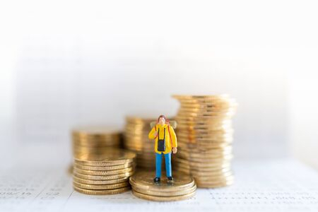 Travel saving and planing concept. Traveler miniature people figure with backpack standing on stack of gold coins on bank passbook with copy space. Zdjęcie Seryjne