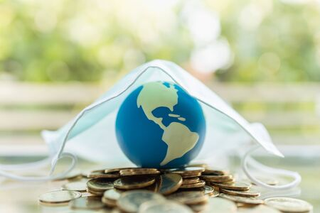 Global Money, Business, Healthcare in Cornavirus (COVID-19) Situation Concept. Mini world ball on pile of gold coins under surgical face mask with copy space.