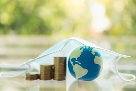 Global Money, Business, Healthcare in Cornavirus (COVID-19) Situation Concept. Mini world ball with stack of gold coins under surgical face mask and green nature background with copy space.