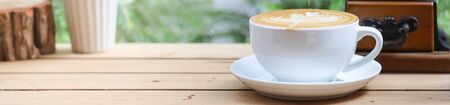 Closeup of white cup of hot coffee latte with milk foam art on wooden table use for cover page concept.