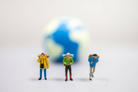 Travel concepts. Three traveler miniature figures people with backpack standing in front of mini world ball on white background with copy space.