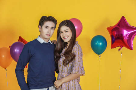 Couple, New Year, Valentine and Holiday Seasoning concept.  Portrait of handsome asian man and  beautiful woman yellow background and colorful party balloon. Stok Fotoğraf