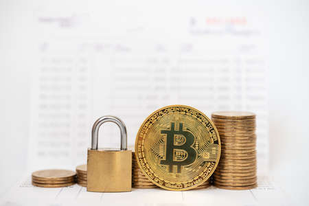 Business , Money, Technology, Security and cryptocurrency Concept. Close up of gold bitcoin coins with master key lock and stack of coins on bank passbook.