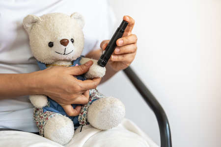 Close up of woman hands using lancet on teddy bear doll hand to check blood sugar level by Glucose meter. Use as Conceptual Medicine, diabetes, glycemia, health care and people concept.