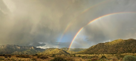 A rare double rainbow appears over Albuquerques Sandia Mountains in the monsoon season photo