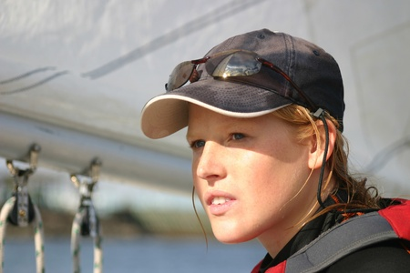 lifevest: Attractive young woman sailing a small sialboat