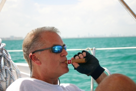 Middle-aged man smoking cigar on sailboat, tropical waters of Biscayne Bay, in background