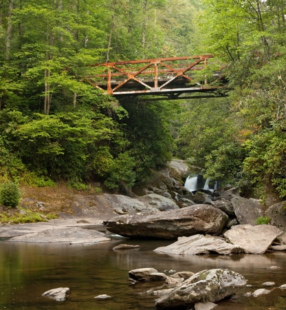 appalachian mountains: An old rusted iron bridge spans the Wild and Scenic Chattooga River in Western North Carolina, in the dense, lush Nantahala National Forest Stock Photo