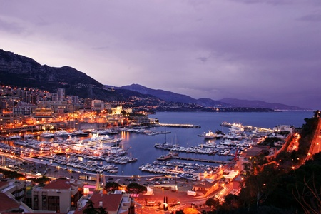 french riviera: Monaco scenic at night including lavish yachts and the Monte Carlo skyline Stock Photo