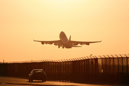 goodbye: Airplane taking off right next to a car driving on a road, at sunset Stock Photo
