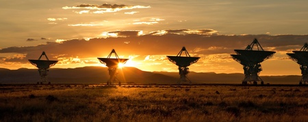 Satellite dishes in the Very Large Array in Socorro, New Mexico, silhouetted against a gold desert sunset