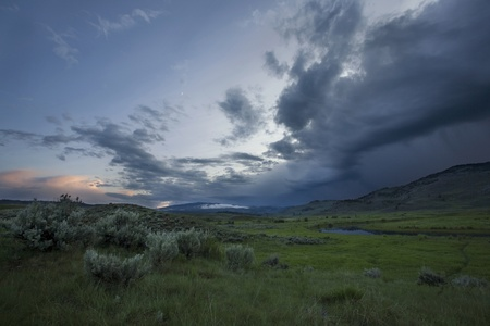 specifically: A storm moves across grassland in Yellowstone National Park, Wyoming.  Specifically, the Lamar Valley portion of Yellowstone Stock Photo
