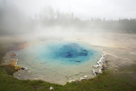 aquifer: Clear, blue, beautiful geyser and misty fog in Yellowstone National Park, Wyoming, USA.