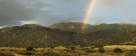 Beautiful rainbow over desert mountains at sunset