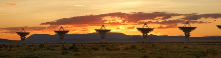 The Very Large Array, which is a large array of satellite dishes that is used to probe deep space, is seen at sunset. photo