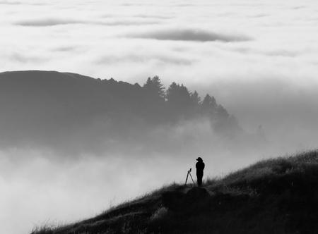 black and white forest: Photographer surveying foggy landscape
