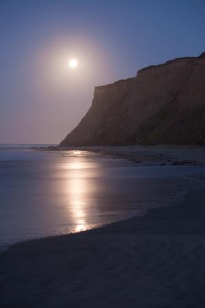 The moon setting at sunrise at Half Moon Bay, California