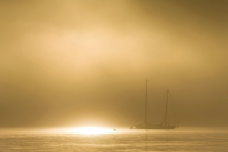 schooner: Schooner sailboat on a golden foggy dawn Stock Photo