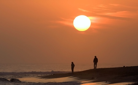 Two people walking on the beach at sunset in Half Moon Bay, California photo
