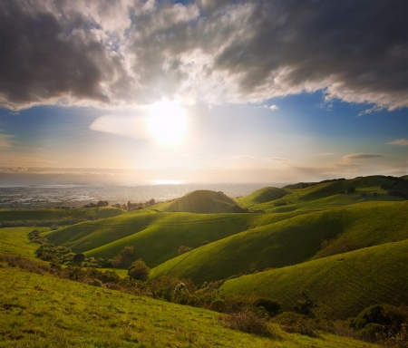 foothills: Spring sunset in lush green meadow in California, viewing the San Francisco Bay from the foothills of the Diablo Range Stock Photo