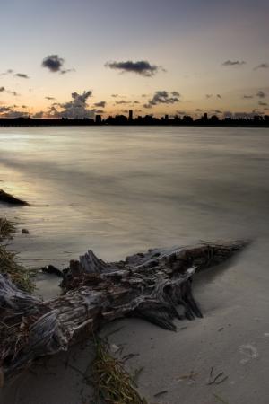 llave de sol: Puesta de sol sobre la playa, trozos de madera y tejados de Miami Foto de archivo