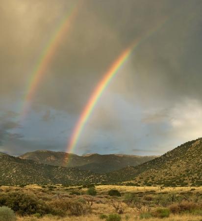 Rare double rainbow over desert mountains at sunset