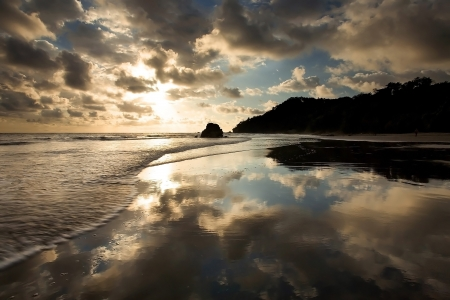 A tropical beach at sunset in Costa Rica, with waves and perfect reflection