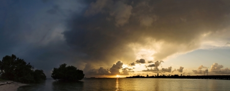 inclement: Large storm looming over Miami skyline at sunset Stock Photo