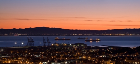 Sunrise in California, over San Francisco Bay and harbor, as seen from Bernal Heights Park   Cargo ships patiently wait to start the day   Oakland is visible across the water  Stock Photo