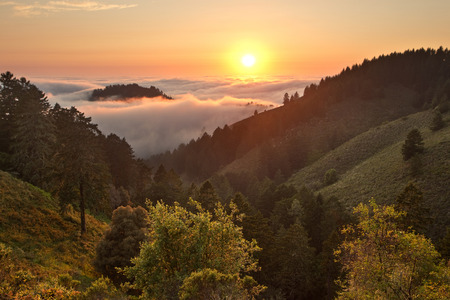 chaparral: Dense fog rolls in over the Pacific Ocean at sunset over coastal California mountains Stock Photo