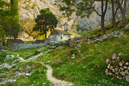 A small ancient church stands in ruin in a lush valley, nested in the mountainous landscape outside of Kotor, Montenegro