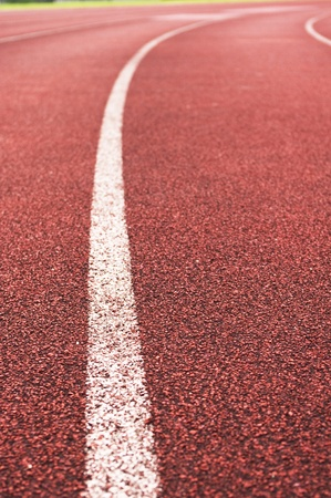 track and field athlete: a close up of white line on red racetrack, for sports, concept background.