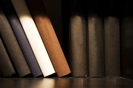 book shelf: a close up shot of book on shelf, indoor setting.