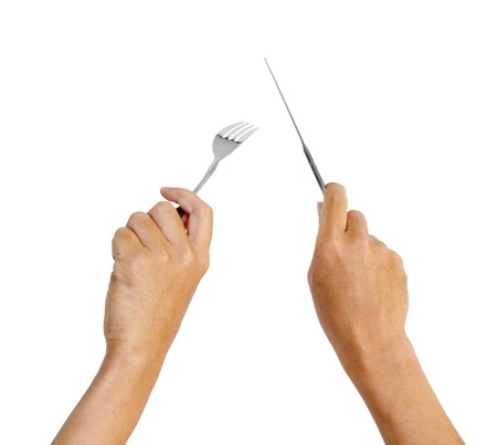 hands holding knife and fork, with movement like cutting a steak photo