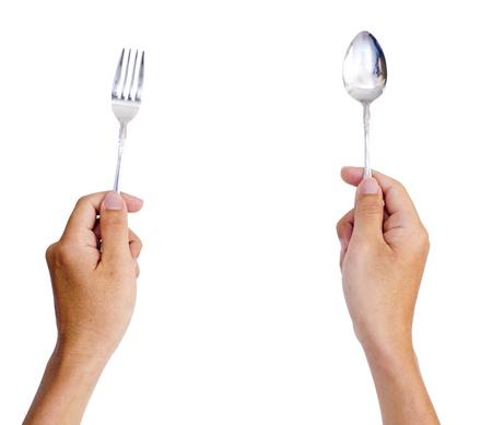 sked: händer håller gaffel och sked, väntar på måltiden. Stockfoto