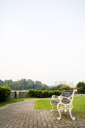 Empty bench in a park, to convey a feeling of waiting or expecting for the future or time passing.  Stock Photo