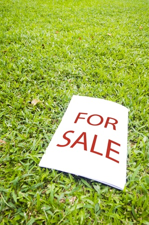 a for sale sign on grass field. For real estate background. photo