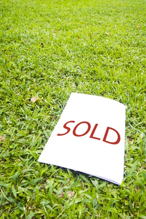 a sold sign on grass field. For real estate background. photo