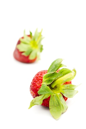 attentions: single isolated strawberry with other strawberries in the background.