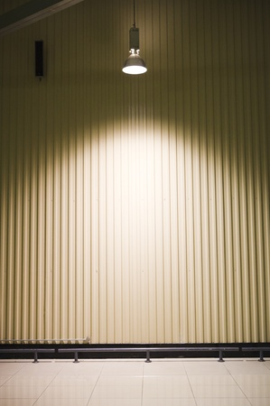 illuminated wall: empty warehouse with a headlight on ceiling  Stock Photo