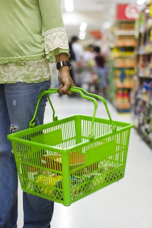grocery basket: shopping in supermarket, carrying a grocery basket