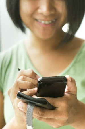 communicating: close up of a woman using her smartphone, with both hand holding.