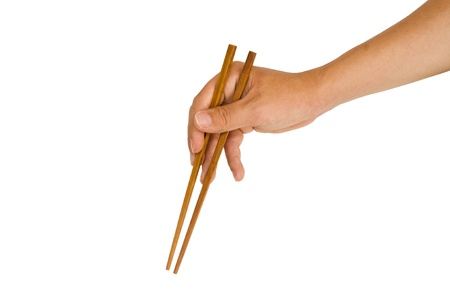 chopstick: isolated man hand holding wooden chopstick, with clipping path in jpg. Stock Photo
