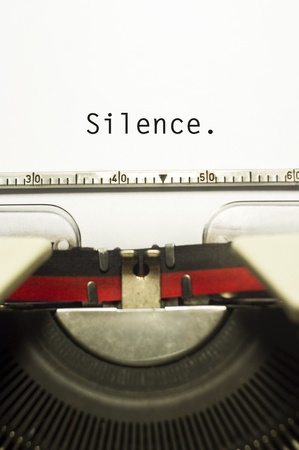 violence in the workplace: silence message is typed on typewriter, for conceptual background. Stock Photo