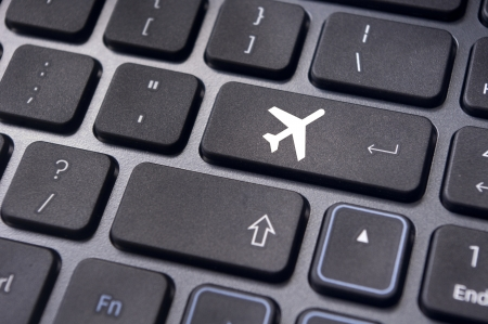 a plane sign on keyboard, to illustrate online booking or purchase of plane ticket or business travel concepts. photo