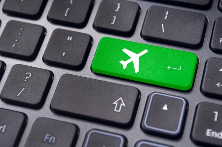 online purchase: a plane sign on keyboard, to illustrate online booking or purchase of plane ticket or business travel concepts.